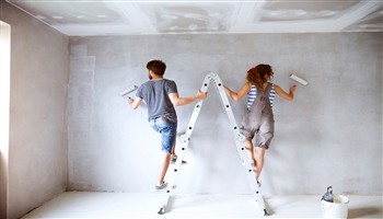 Couple painting a lounge on a ladder