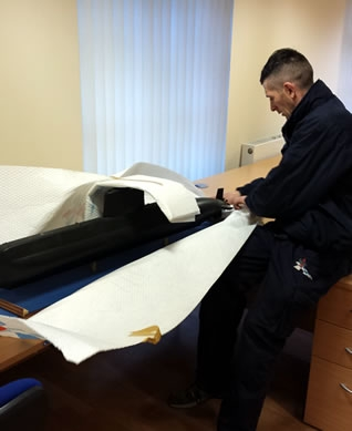 Bishop's Move wrapping a model submarine for protection during it's relocation